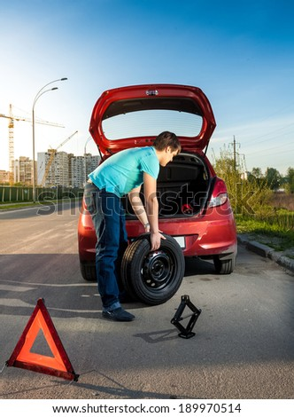 Photo of man changing punctured wheel on broken car - stock photo