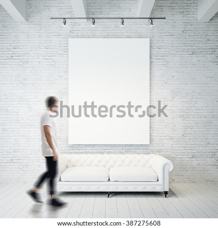 Photo of man in gallery. Waching empty canvas hanging on the brick wall and vintage classic sofa wood floor. Square, blank mockup. Motion blur - stock photo
