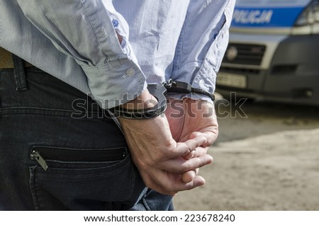 Photo of man in handcuffs. - stock photo