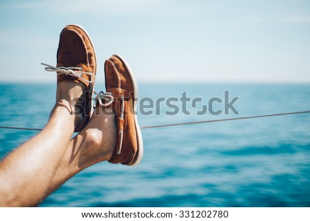 Photo of man legs on the yacht and wearing boat shoes - stock photo