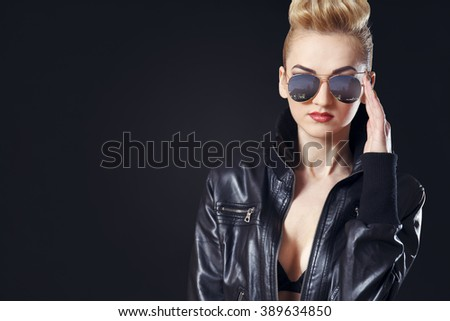Photo of mature attractive blonde girl wearing opened leather jacket with bra showing and sunglasses, having trimmed hair on sides. - stock photo