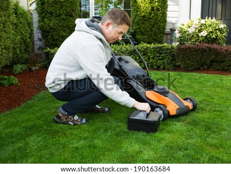 Photo of mature man putting in battery in electric lawnmower on freshly cut plush green grass with home in background  - stock photo
