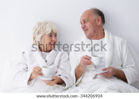 Photo of mature marriage relaxing together in bed