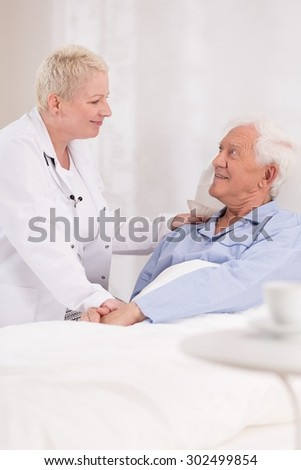 Photo of mature nurse taking care about old patient - stock photo