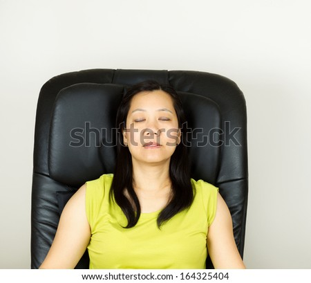 Photo of mature woman relaxing in massage chair, eyes closed, with wall in background  - stock photo