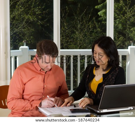 Photo of mature woman showing man where to sign document while working at home with laptop, calculator and papers on top of table and large windows in background - stock photo