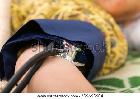 Photo of measuring the elderly womans blood pressure  - stock photo