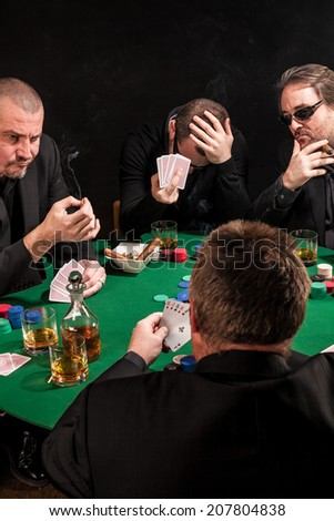 Photo of men playing poker, drinking and smoking, and looking uncertain of their luck. - stock photo