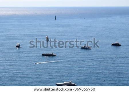 Photo of modern and classic yachts sailing boats vessels offshore in calm blue sea silhouetted against clear sky day time on beautiful seascape background, horizontal picture - stock photo