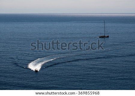 Photo of modern and classic yachts sailing boats vessels offshore in calm blue sea silhouetted against evening clear sky on seascape background, horizontal picture - stock photo