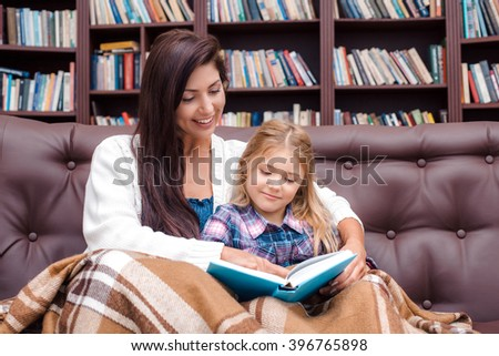 Photo of mother and little daughter. Nice cozy interior with big bookcase. Mother and daughter reading bedtime story - stock photo