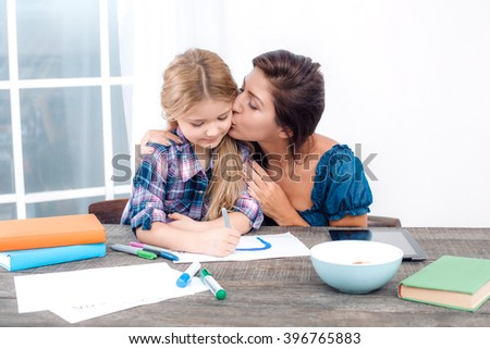 Photo of mother and little daughter using tablet computer. Nice white interior with wooden table. Mother kissing her daughter