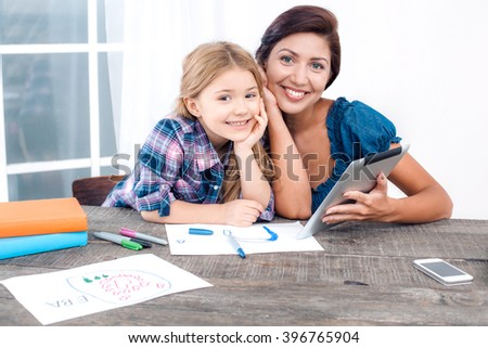 Photo of mother and little daughter using tablet computer. Nice white interior with wooden table. Mother and daughter looking at camera and smiling - stock photo