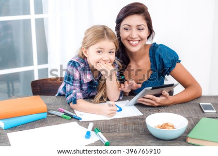 Photo of mother and little daughter using tablet computer. Nice white interior with wooden table. Daughter laughing - stock photo