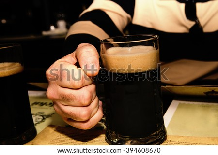 photo of Mug of dark beer in hand  - stock photo