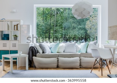 Photo of new comfortable sofa with light decorative cushions - stock photo