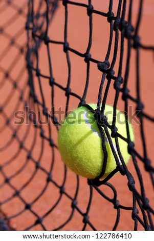 Photo of new tennis ball struck in tenis net on a clay court