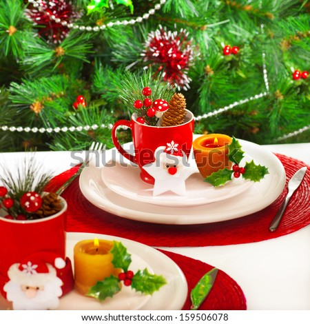 Photo of New Year event banquet, beautiful white plates with Cristmas decoration on holiday setting table, decorated evergreen tree at home in xmas eve, christmastime ornament - stock photo