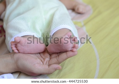 Photo of newborn baby feet on mother hand - stock photo