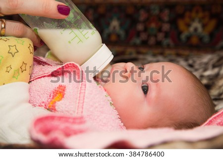 photo of newborn baby sucking bottle - stock photo