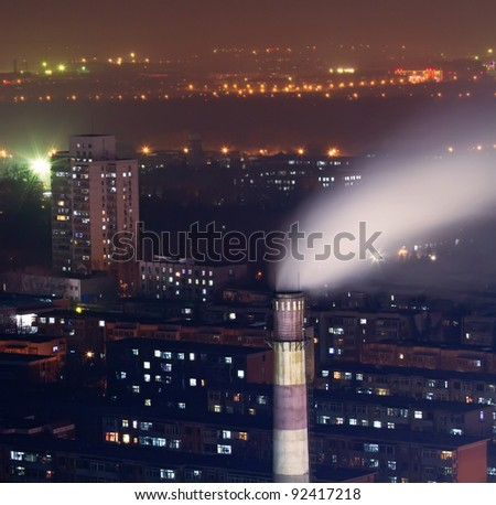 Photo of night scene of chimney with smoke in residents area in heavy fog - stock photo