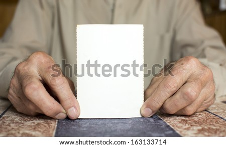 Photo of old man holding blank paper  - stock photo
