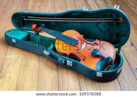 Photo of old violin in case on a wooden floor - stock photo