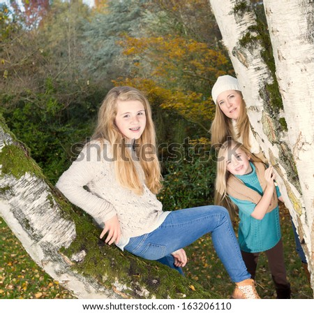 Photo of oldest daughter sitting in middle of tree with mother and younger daughter in background  - stock photo