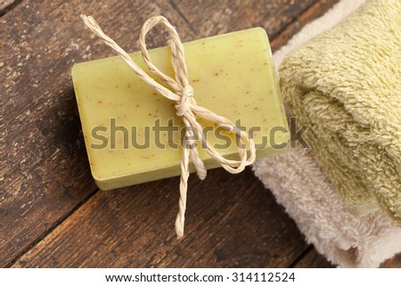 Photo of olive soap and towels over wooden table - stock photo