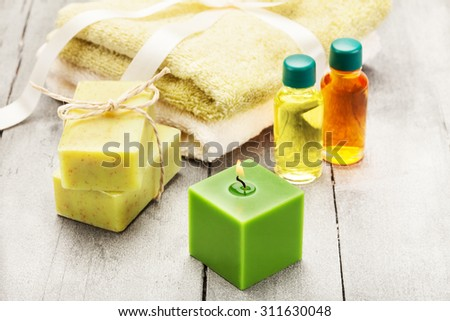 Photo of olive soap end essential oil over wooden table - stock photo
