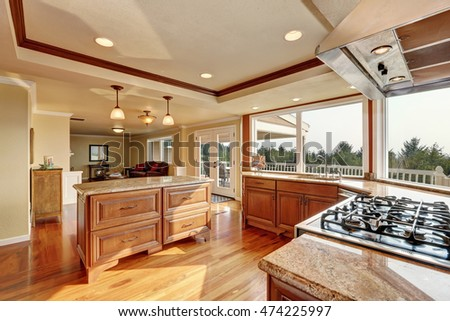 Photo of open concept kitchen with cabinets, granite counter tops, hardwood floors and an island. Window view. Northwest, USA