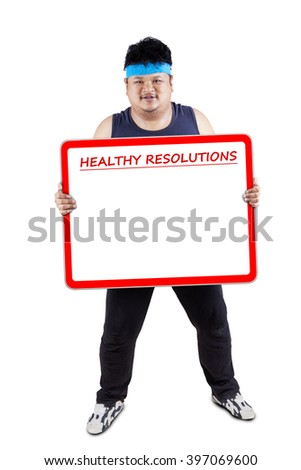 Photo of overweight man standing in the studio while holding a board of healthy resolutions with copy space