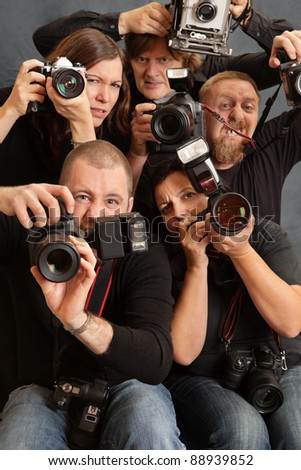 Photo of paparazzi fighting for space to take photos. Focus is on the face of the male in front. - stock photo