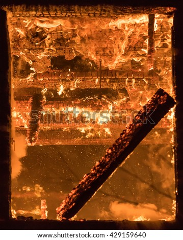 Photo of Part of a House on Fire. Window view to Fire Inside Wooden Old House - stock photo