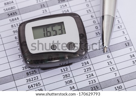 Photo Of Pedometer With Pen Over Document