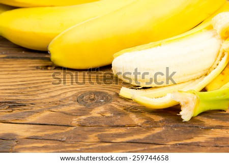 Photo of peeled bananas on wooden board - stock photo
