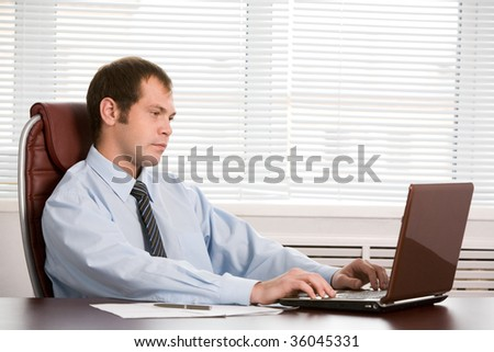 Photo of pensive boss looking at laptop screen while working in office