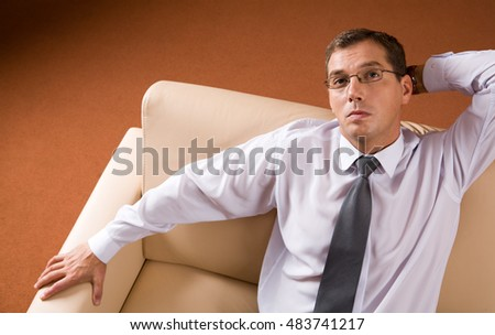 Photo of pensive boss sitting on sofa in his workshop and thinking about business