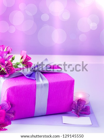 Photo of pink gift box with purple silk ribbon, beautiful violet wild flowers bouquet, candle and white blank greeting card on the table at home, festive blur background, mothers day, love concept - stock photo