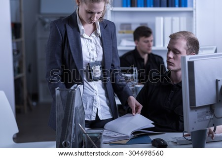 Photo of policewoman with badge working on new case - stock photo
