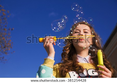 photo of Portrait of stylish young girl blowing soap bubbles on street