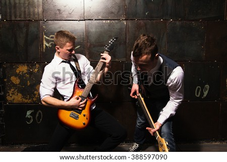 photo of portrait of Two young musicians  with guitar on black background - stock photo
