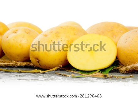 Photo of potatoes with slice on wooden board with white space