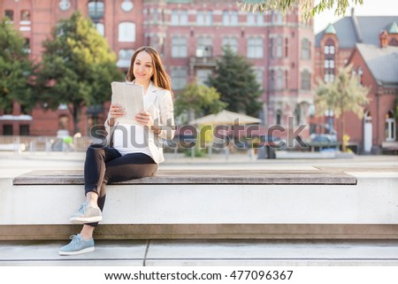 Photo of pregnant businesswoman  reading thenewspaper on a bench
