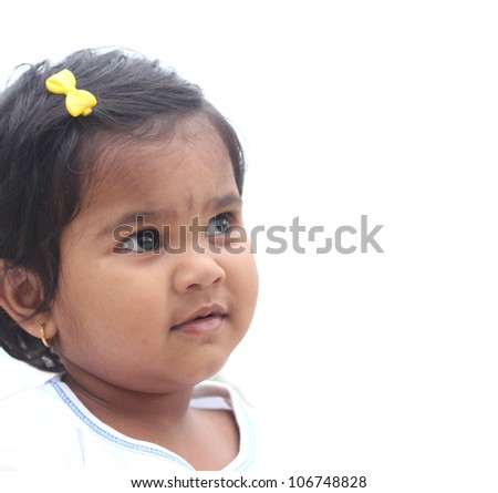 Photo of pretty and happy indian girl child. The picture can be used to show the baby day dreaming or the toddler imagining something or as a child with a vision, etc. The child is of pre-school age. - stock photo