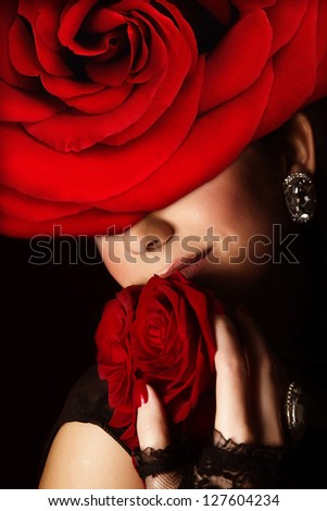 Photo of pretty arabic woman wearing stylish red floral hat, closeup portrait of attractive female with fresh roses bouquet, romantic gift for Valentine day holiday, beauty salon, fashion concept - stock photo
