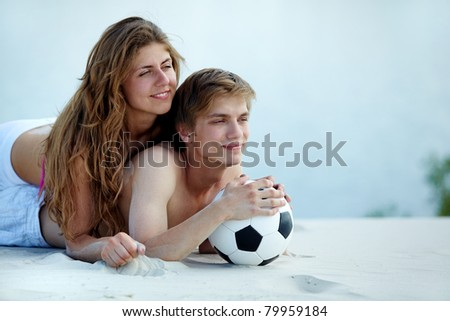 Photo of pretty girl and handsome guy with ball lying on sandy beach - stock photo