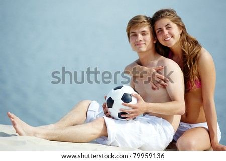 Photo of pretty girl embracing handsome male with ball and both looking at camera - stock photo