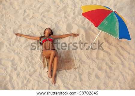 Photo of pretty girl in swimsuit lying on sandy beach with colorful beach umbrella near by