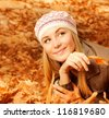 Photo of pretty girl lying down on the ground covered dry autumnal foliage - stock photo